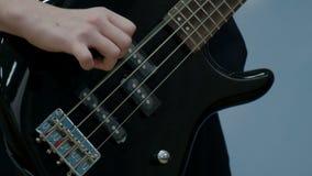 Primo piano delle dita di un adolescente che gioca un basso elettrico elettrico nero Il tipo ha tirato le corde su un musical archivi video