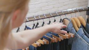 Primo piano delle dita femminili che toccano i vestiti, su un gancio in un deposito o in un guardaroba stock footage