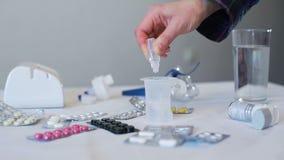 Primo piano delle droghe di gocciolamento nel becher della medicina archivi video