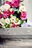 Primo piano delle fedi nuziali sul mazzo di nozze del fondo delle rose delle bacche e dei verdi con lavanda immagine stock