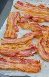 Primo piano delle fette appetitose di bacon affumicato Isolato su priorit? bassa bianca fotografie stock libere da diritti