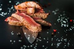 Primo piano delle fette rare medie della bistecca su un coltello Immagini Stock Libere da Diritti