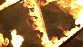 Primo piano delle fiamme del fuoco sulla costruzione bruciante del metallo con la foresta su fondo archivi video