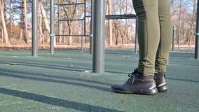 Primo piano delle gambe della ragazza in uno spazio all'aperto per l'allenamento alla barra orizzontale archivi video