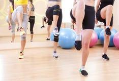 Primo piano delle gambe di quattro atleti femminili caucasici che hanno corpo che allunga gli esercizi Immagine Stock