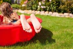 Primo piano delle gambe di una bambina in piccolo stagno rosso Fotografia Stock Libera da Diritti