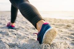 Primo piano delle gambe femminili in calzamaglia e scarpe da tennis nel corso della mattinata ex Fotografia Stock