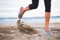Primo piano delle gambe femminili che corrono sulla spiaggia all'alba nella mattina con in-moto della sabbia Immagini Stock