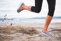 Primo piano delle gambe femminili che corrono sulla spiaggia all'alba nella mattina con in-moto della sabbia Fotografia Stock
