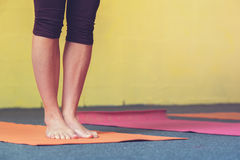 Primo piano delle gambe femminili sulla stuoia di esercizio Fotografie Stock