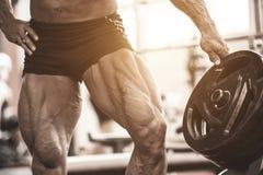 Primo piano delle gambe muscolari dei culturisti Uomo dell'atleta che fa esercizio di allenamento in palestra Fotografia Stock Libera da Diritti