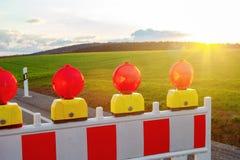 Primo piano delle luci d'avvertimento della via alla strada sulla campagna Fotografia Stock