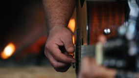 Primo piano delle mani che giocano chitarra davanti ad un camino, vista laterale archivi video