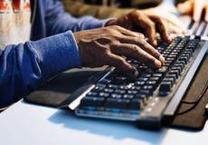 Primo piano delle mani che lavorano alla tastiera di computer fotografie stock