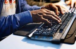 Primo piano delle mani che lavorano alla tastiera di computer immagini stock