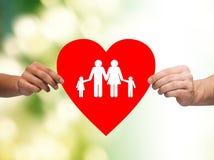 Primo piano delle mani che tengono cuore rosso con la famiglia Fotografie Stock Libere da Diritti