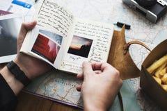 Primo piano delle mani che tengono il taccuino del diario di viaggio sopra il backgro della mappa immagini stock libere da diritti