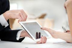 Primo piano delle mani con la compressa ed il computer portatile Fotografia Stock Libera da Diritti