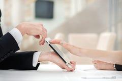 Primo piano delle mani con la compressa ed il computer portatile Uomini d'affari sui corpus Fotografia Stock