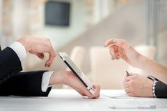 Primo piano delle mani con la compressa ed il computer portatile Uomini d'affari sui corpus Fotografie Stock Libere da Diritti