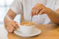 Primo piano delle mani con le tazze di caffè in caffè Immagini Stock Libere da Diritti