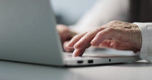 Primo piano delle mani corrugate di una donna anziana di affari che scrive su una tastiera video d archivio
