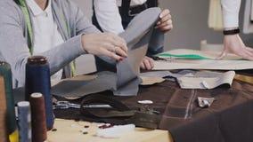 Primo piano delle mani degli stilisti dei tailores che lavorano con il materiale grigio facendo uso degli schizzi, essi che si si video d archivio
