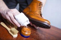 Primo piano delle mani degli uomini che lucidano Derby Brogue Boots abbronzato di cuoio usando varietà di spazzole e polacco cera fotografia stock