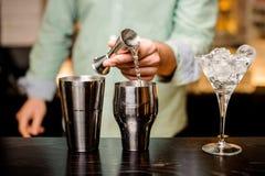 Primo piano delle mani del barista che versano bevanda in un jigger per preparare un cocktail Fotografie Stock