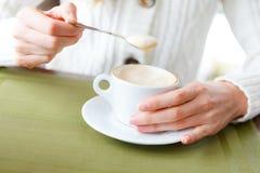 Primo piano delle mani del caffè e della donna della tazza Fotografia Stock