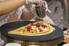 Primo piano delle mani del cuoco in guanti che preparano crêpe, pancake sulla padella con la banana fresca, mirtillo, lampone fotografie stock