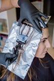 Primo piano delle mani del parrucchiere che applicano tintura per capelli a Fotografie Stock