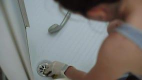 Primo piano delle mani della casalinga con i guanti che puliscono il lavandino della doccia stock footage