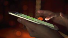 Primo piano delle mani della donna facendo uso dello schermo attivabile al tatto dello smartphone all'aperto in città alla notte  video d archivio