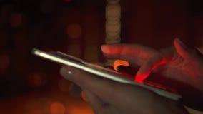 Primo piano delle mani della donna facendo uso dello schermo attivabile al tatto dello smartphone all'aperto in città alla notte  stock footage