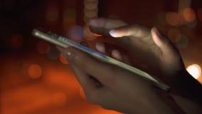 Primo piano delle mani della donna facendo uso dello schermo attivabile al tatto dello smartphone all'aperto in città alla notte  archivi video