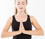 Primo piano delle mani della donna graziosa, ragazza in maglietta, meditante all'interno, fuoco su braccia nel gesto di Namaste M immagine stock