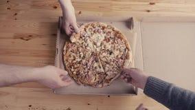 Primo piano delle mani della gente che prendono la pizza delle fette dalla scatola aperta di consegna dell'alimento Servizio sapo stock footage