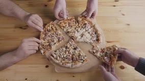 Primo piano delle mani della gente che prendono la pizza delle fette dalla scatola aperta di consegna dell'alimento Servizio sapo video d archivio