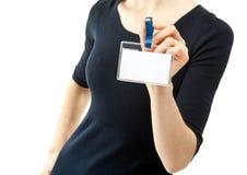 Primo piano delle mani della giovane donna che mostrano distintivo in bianco Fotografia Stock