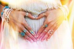 Primo piano delle mani della giovane donna nella forma del cuore con il lotto del porcile di boho Immagini Stock