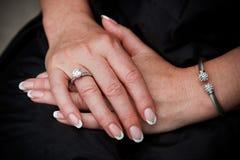 Primo piano delle mani della sposa Immagine Stock