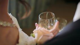 Primo piano delle mani dello sposo e della sposa che tengono i vetri del champagne e che tostano sul giorno delle nozze stock footage