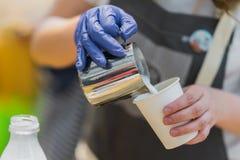 Primo piano delle mani di barista, preparante il latte di versamento del cappuccino adeguato con schiuma nella tazza di caffè Pre Immagini Stock