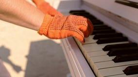 Primo piano delle mani di un giocatore di piano con i guanti che giocano sulla tastiera Mani del ` s degli uomini con i guanti su video d archivio
