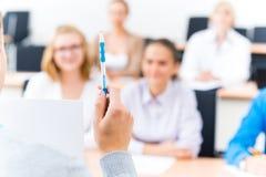 Primo piano delle mani di un insegnante con una penna Immagini Stock Libere da Diritti