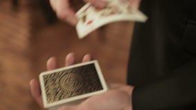 Primo piano delle mani di un mago che eseguono trucco di carta video d archivio