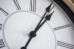 Primo piano delle mani di un orologio di parete di legno con i numeri romani fotografia stock libera da diritti