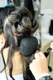 Primo piano delle mani di un parrucchiere professionista che fanno un'acconciatura in un salone di bellezza fotografia stock libera da diritti