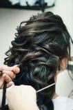 Primo piano delle mani di un parrucchiere professionista che fanno un'acconciatura in un salone di bellezza Castana di modello, n fotografia stock